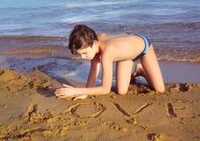 Ragazzo sul gioco di esposizione al sole della presa della spiaggia con la sabbia Fotografia Stock