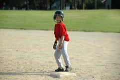 Ragazzo sulla base sul gioco di baseball Fotografia Stock