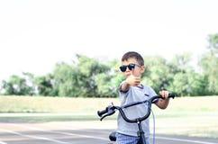 Ragazzo sulla bici con i pollici su fotografia stock