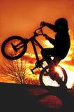 Ragazzo sulla siluetta di BMX Fotografia Stock
