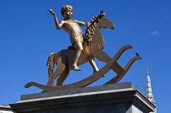 Ragazzo sulla statua del cavallo di oscillazione nel quadrato di Trafalgar Fotografia Stock