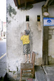 Ragazzo sulla via Art Mural della sedia a Georgetown, Penang, Malesia Fotografia Stock Libera da Diritti