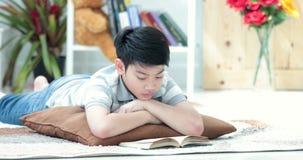 Ragazzo sveglio asiatico che legge un libro sul fronte di sorriso del briciolo del pavimento a casa stock footage