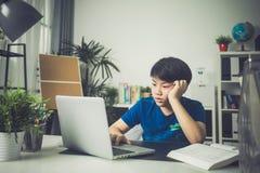 Ragazzo sveglio asiatico che per mezzo del computer portatile Fotografia Stock