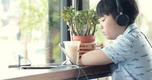 Ragazzo sveglio asiatico che per mezzo del telefono cellulare e sorseggiando latte nella tazza e nei sorrisi Concetto di: rete so archivi video