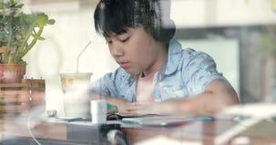 Ragazzo sveglio asiatico che per mezzo del telefono cellulare e sorseggiando latte nella tazza e nei sorrisi Concetto di: rete so stock footage
