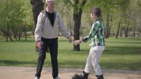 Ragazzo sveglio in camicia a quadretti che rollerblading nel parco, suo nonno che prende lui ed abbracciare Svago attivo all'aper video d archivio