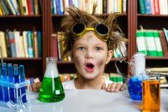 Ragazzo sveglio che effettua ricerca in biochimica in chimica fotografia stock libera da diritti