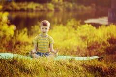 Ragazzo sveglio che fa yoga sul fondo della natura Ragazzino sportivo che fa gli esercizi nel parco di estate Fotografie Stock