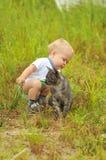 Ragazzo sveglio che gioca con un gatto fotografia stock