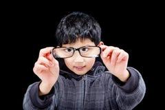 Ragazzo sveglio che guarda tramite gli occhiali fotografia stock