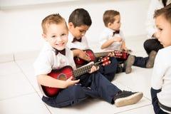 Ragazzo sveglio che impara come giocare chitarra Fotografia Stock Libera da Diritti