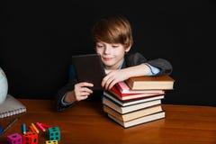 Ragazzo sveglio che legge un libro elettronico e che si siede ad uno scrittorio della scuola Di nuovo al banco Fotografia Stock