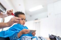 Ragazzo sveglio che ottiene un taglio dei capelli in Barber Shop Concetto di bellezza fotografia stock libera da diritti
