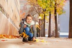 Ragazzo sveglio che raccoglie le foglie di acero sulla sua via di casa Immagine Stock