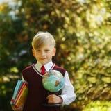 Ragazzo sveglio che ritorna a scuola Bambino con i libri ed il globo su abete Fotografie Stock