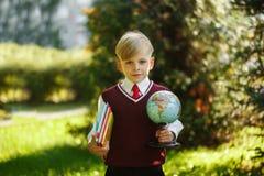 Ragazzo sveglio che ritorna a scuola Bambino con i libri ed il globo sul primo giorno di scuola Fotografia Stock Libera da Diritti