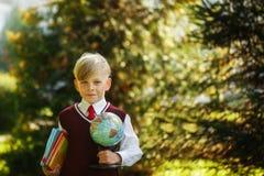 Ragazzo sveglio che ritorna a scuola Bambino con i libri ed il globo sul primo giorno di scuola Fotografia Stock