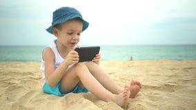 Ragazzo sveglio che si siede alla spiaggia sabbiosa e che per mezzo del app dello smartphone video d archivio