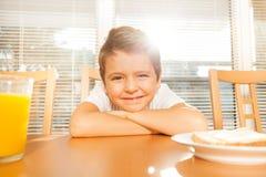 Ragazzo sveglio che si siede alla tavola con la sua prima colazione Immagine Stock