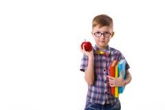 Ragazzo sveglio cinque anni con i libri e la mela Immagine Stock