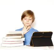 Ragazzo sveglio con i libri e la compressa elettronica Fotografia Stock