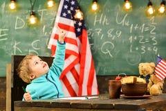 Ragazzo sveglio con la bandiera americana sulla lavagna alla lezione della scuola Fotografia Stock