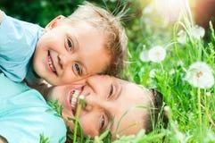 Ragazzo sveglio con la madre che si trova nell'erba Fotografie Stock Libere da Diritti