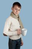 Ragazzo sveglio con una tazza bianca su fondo blu Fotografia Stock