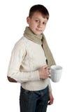 Ragazzo sveglio con una tazza isolata su fondo bianco Immagini Stock