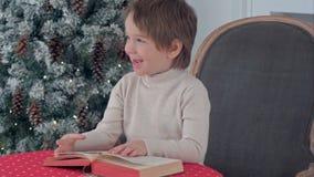 Ragazzo sveglio del bambino che esamina i puctures nel libro che si siede su una sedia vicino all'albero di Natale Fotografia Stock