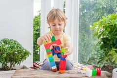 Ragazzo sveglio del bambino con il gioco con i lotti dei blocchi di plastica variopinti dell'interno Bambino attivo divertendosi  Immagini Stock