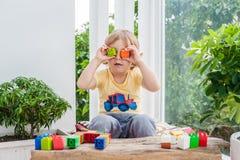 Ragazzo sveglio del bambino con il gioco con i lotti dei blocchi di plastica variopinti dell'interno Bambino attivo divertendosi  Fotografie Stock