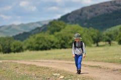 Ragazzo sveglio del bambino con lo zaino che cammina su un piccolo percorso in montagne Escursione del bambino Immagine Stock