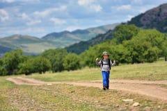 Ragazzo sveglio del bambino con lo zaino che cammina su un piccolo percorso in mountai Fotografia Stock