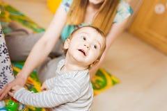 Ragazzo sveglio del bambino e della madre che gioca insieme dell'interno fotografie stock