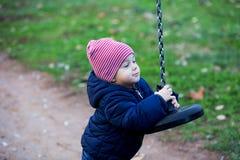 Ragazzo sveglio del bambino in vestiti caldi di autunno divertendosi con il triciclo immagini stock