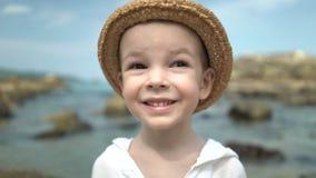 Ragazzo sveglio del ritratto in un cappello di paglia sulla spiaggia stock footage