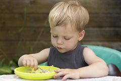 Ragazzo sveglio felice del bambino del bambino che mangia porridge stesso con il cucchiaio fotografie stock libere da diritti