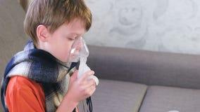 Ragazzo sveglio malato che inala attraverso la maschera dell'inalatore Utilizzi il nebulizzatore e l'inalatore per il trattamento video d archivio