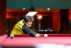 Ragazzo sveglio nel biliardo giallo dei giochi della maglietta o stagno in club Il ragazzino impara giocare lo snooker Ragazzo co fotografia stock