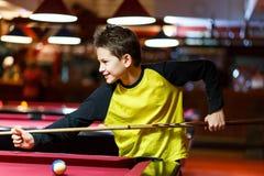 Ragazzo sveglio nel biliardo giallo dei giochi della maglietta o stagno in club Il ragazzino impara giocare lo snooker Ragazzo co immagini stock libere da diritti