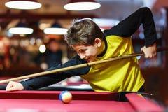 Ragazzo sveglio nel biliardo giallo dei giochi della maglietta o stagno in club Il ragazzino impara giocare lo snooker Ragazzo co fotografie stock