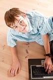 Ragazzo teenaged sveglio che per mezzo del computer sul pavimento Fotografie Stock