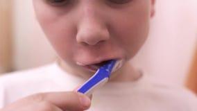 Ragazzo teenager che pulisce i suoi denti nel bagno stock footage