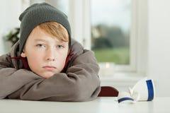 Ragazzo teenager che si appoggia tavolo da cucina con la tazza rotta fotografia stock libera da diritti
