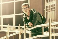 Ragazzo teenager con lo zaino contro un edificio scolastico Fotografia Stock Libera da Diritti