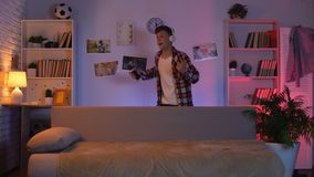 Ragazzo teenager in cuffie che ascolta la musica e ballare, fingenti di essere famoso video d archivio