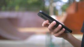 Ragazzo teenager da solo facendo uso di un telefono cellulare contro lo sfondo di un parco del pattino mentre altri bambini attiv stock footage