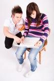 Ragazzo teenager e ragazza con il computer portatile Fotografia Stock